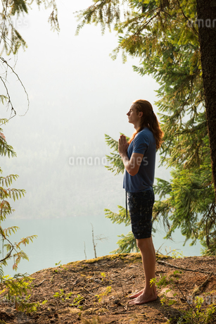 Fit man standing in meditating posture on the edge of a rockの写真素材 [FYI02705167]
