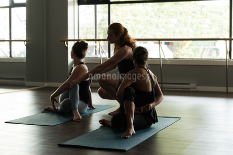 Trainer assisting people in practicing yogaの写真素材 [FYI02705185]