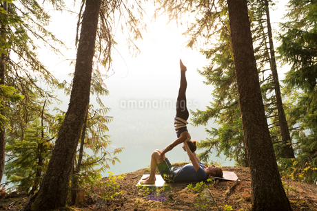 Sporty couple practicing acro yoga in a lush green forestの写真素材 [FYI02705198]