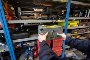 Male aircraft maintenance engineer removing a tool from shelf at airlines maintenance facilityの写真素材 [FYI02705213]