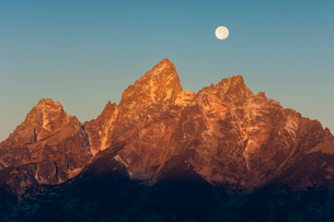 A jagged mountain range in the Grand Teton national park at night, with a full moon in the sky.の写真素材 [FYI02705216]
