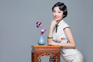 Young beautiful woman in traditional cheongsam with orchidの写真素材 [FYI02705254]