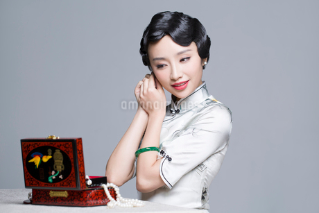 Young beautiful woman in traditional cheongsam dressing up herselfの写真素材 [FYI02705273]