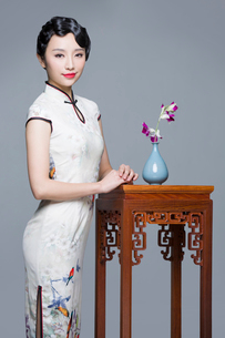 Young beautiful woman in traditional cheongsam with orchidの写真素材 [FYI02705293]