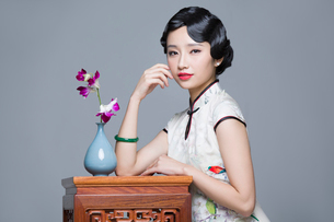 Young beautiful woman in traditional cheongsam with orchidの写真素材 [FYI02705311]