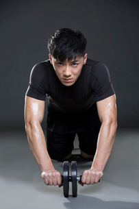 Young man exercising with Ab wheelの写真素材 [FYI02705315]