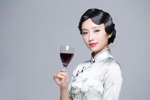 Young beautiful woman in traditional cheongsam with red wineの写真素材 [FYI02705324]