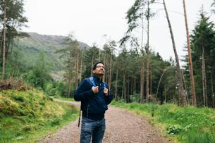 Man standing on a rural road in Glen Coe, Scotlandの写真素材 [FYI02705325]