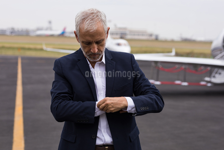 Businessman buttoning his shirt sleeves on a runawayの写真素材 [FYI02705332]