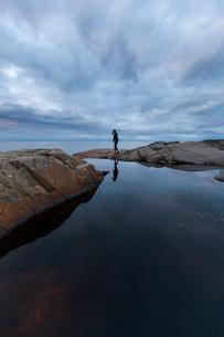 Woman standing by a rock pool in Vasterbotten, Swedenの写真素材 [FYI02705372]