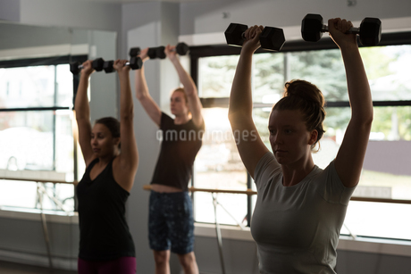 Trainer assisting women in exercising with dumbbellsの写真素材 [FYI02705379]