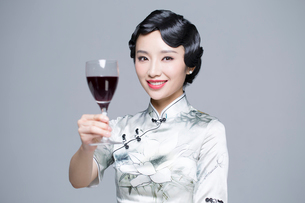 Young beautiful woman in traditional cheongsam with red wineの写真素材 [FYI02705381]