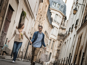 A couple walking along a narrow street in a historic city centre, with shopping bags.の写真素材 [FYI02705393]
