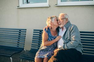 Senior couple kissing on benchの写真素材 [FYI02705398]