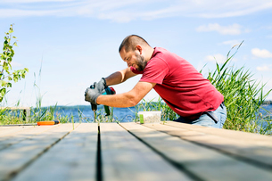 Mid adult man drilling a hole in a deck in Finlandの写真素材 [FYI02705418]