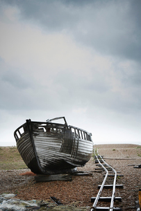 Abandoned wooden boat beached on the shingle by an old narrow gauge track.の写真素材 [FYI02705421]