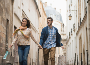 A couple walking along a narrow street in a historic city centre, with shopping bags.の写真素材 [FYI02705423]