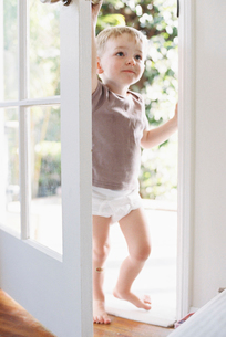 Young boy wearing T-Shirt and pants, opening a door.の写真素材 [FYI02705449]