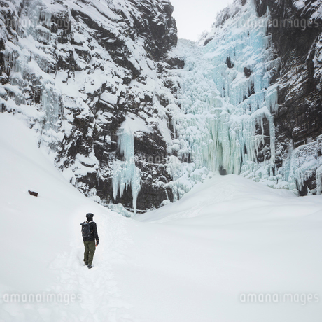 Man beside frozen waterfall in Fulufjallet National Park, Swedenの写真素材 [FYI02705487]
