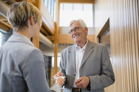 Business people exchanging business cards in office lobbyの写真素材 [FYI02705543]