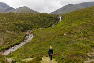 Woman standing in field by river on Isle of Skye, Scotlandの写真素材 [FYI02705545]
