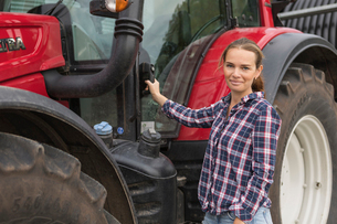 Agricultural worker standing next to a tractor in fieldの写真素材 [FYI02705557]