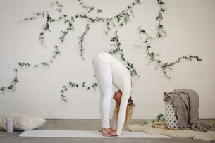 A blonde woman in a white leotard and leggings in a yoga position, bending forwards and down.の写真素材 [FYI02705563]