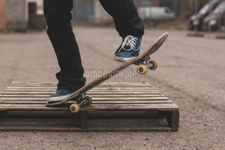Skater doing manual trick on wooden crateの写真素材 [FYI02705574]