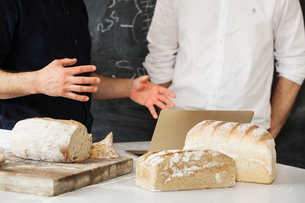 Close up of two bakers standing at a table, using a laptop computer, freshly baked bread.の写真素材 [FYI02705578]