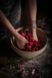 Valentine's Day baking, woman preparing fresh raspberries in a bowl.の写真素材 [FYI02705604]