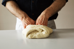 Close up of a baker kneading bread dough.の写真素材 [FYI02705612]