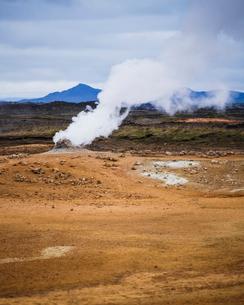 Iceland, Nordurland eystra, Hverarond, Steam over hot springs with mountain range on horizonの写真素材 [FYI02705628]