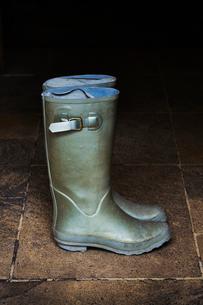 Pair of green Wellington boots standing on stone floor.の写真素材 [FYI02705650]