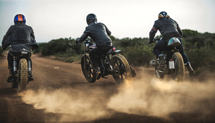 Rear view of three men riding cafe racer motorcycles along dusty dirt road.の写真素材 [FYI02705666]