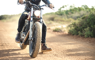 Low section view of man riding cafe racer motorcycle on a dusty dirt road.の写真素材 [FYI02705674]