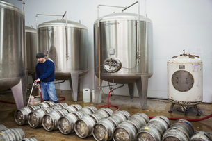 A man filling metal beer kegs from large fermentation tanks in a brewery.の写真素材 [FYI02705676]
