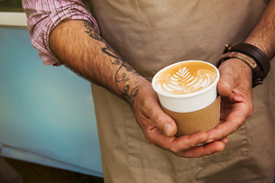 Close up of man with tattoo on his arm holding paper cup with cafe latte.の写真素材 [FYI02705688]