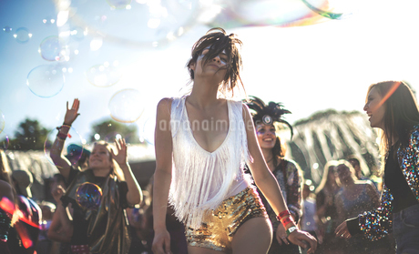 Young woman at a summer music festival wearing golden sequinned hot pants, dancing among the crowd.の写真素材 [FYI02705706]
