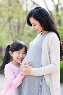 Little girl listening to the fetal heartbeatの写真素材 [FYI02705718]