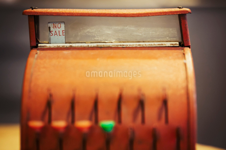 A retro style bronze coloured cash register, an old fashioned till with keys and a glass display.の写真素材 [FYI02705740]