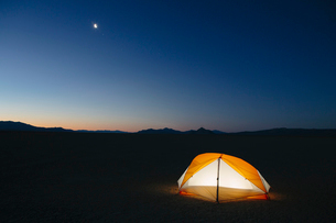 Illuminated camping tent in vast desert at dusk, Black Rock Desert, Nevadaの写真素材 [FYI02705745]