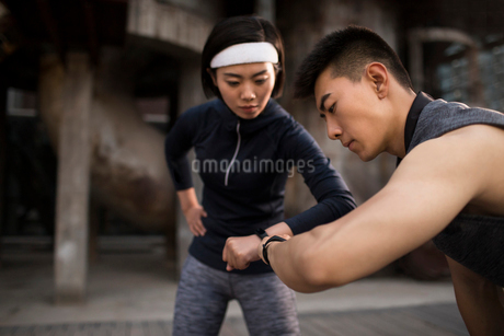 Young Chinese couple checking smart watch after runningの写真素材 [FYI02705749]