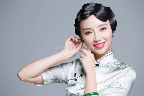 Young beautiful woman in traditional cheongsam dressing up herselfの写真素材 [FYI02705791]