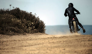 Rear view of man wearing crash helmet and black leathers riding cafe racer motorcycle on a dusty dirの写真素材 [FYI02705811]