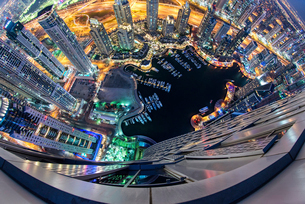 Aerial fish-eye view of Dubai, United Arab Emirates at night, with illuminated skyscrapers and marinの写真素材 [FYI02705814]