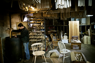 A man working in a furniture maker's workshop. Windsor chairs.の写真素材 [FYI02705849]