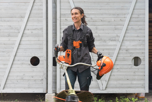 A woman with safety gear and a line trimmerの写真素材 [FYI02705892]