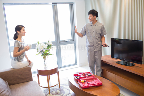 Engineer repairing television in customer's homeの写真素材 [FYI02705909]