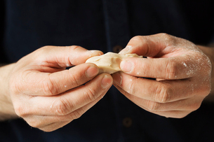 Close up of a baker holding pieces of fresh yeast in his hands.の写真素材 [FYI02705912]
