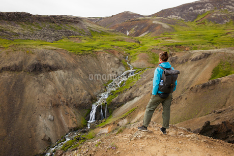 Iceland, Sudurland, Hveragerdi, Reykjadalur, Tourist looking at stream and waterfalls in rocky valleの写真素材 [FYI02705914]